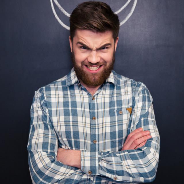 """Portrait of handsome man pretending devil standing over chalkboard background"" stock image"