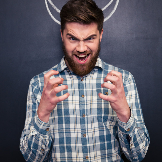 """""""Shouting man standing over chalkboard background with drawn horns"""" stock image"""