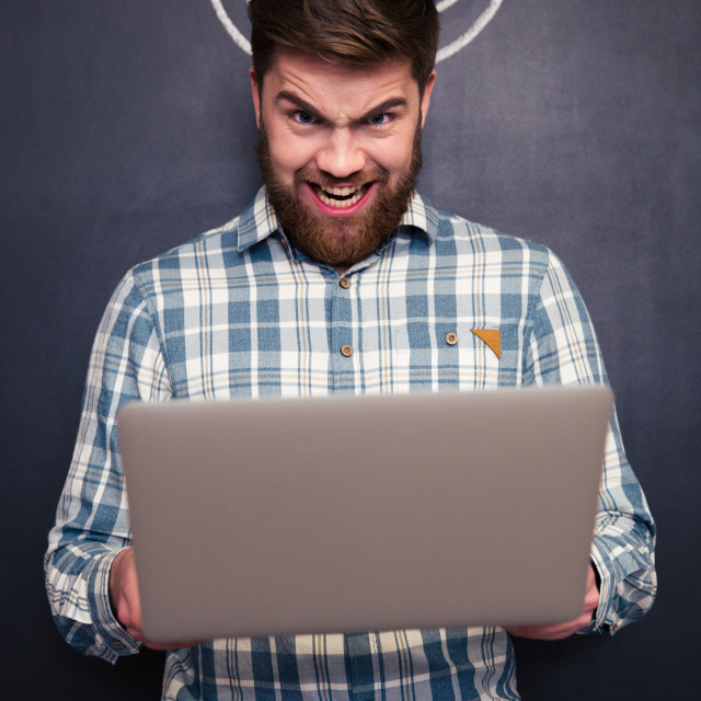 """""""Funny man using laptop over blackboard background with drawn horns"""" stock image"""