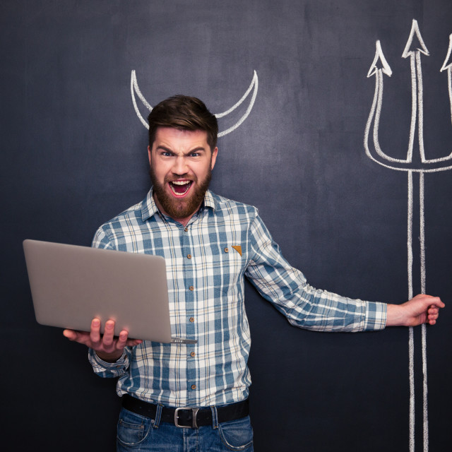"""""""Angry man using laptop and holding trident drawn on blackboard"""" stock image"""