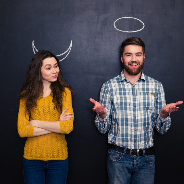 """""""Happy couple playing devil and angel over blackboard background"""" stock image"""