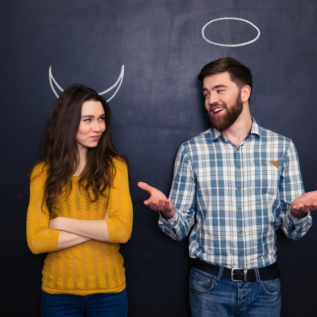 """Smiling couple imitating devil and angel over chalkboard background"" stock image"