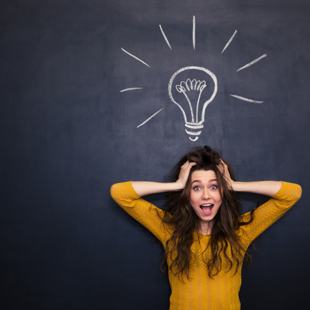 """""""Excited woman with tousled hair standing over blackboard background"""" stock image"""