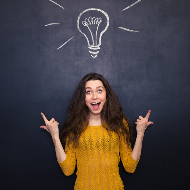 """""""Happy surprised woman ponting up over chalkboard background"""" stock image"""