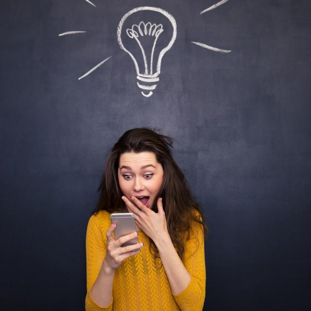 """Amazed happy woman using mobile phone over chalkboard background"" stock image"