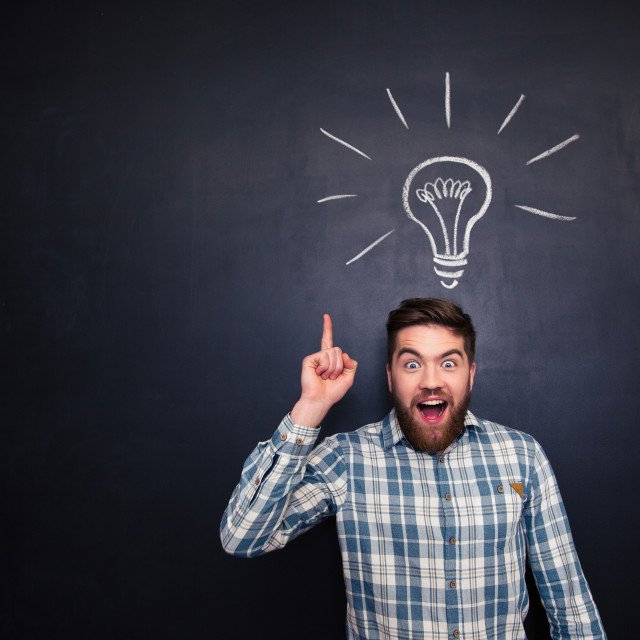 """""""Excited man pointing up over blackboard background with light bulb"""" stock image"""