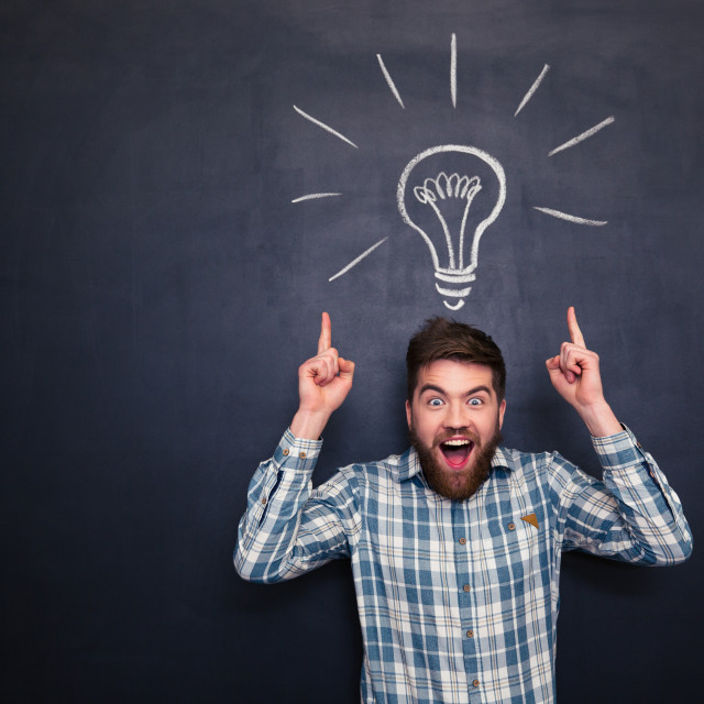 """""""Surprised man pointing up with both hands over chalkboard background"""" stock image"""
