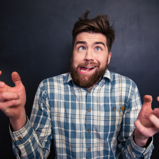 """Ugly bearded man grimacing over black background"" stock image"
