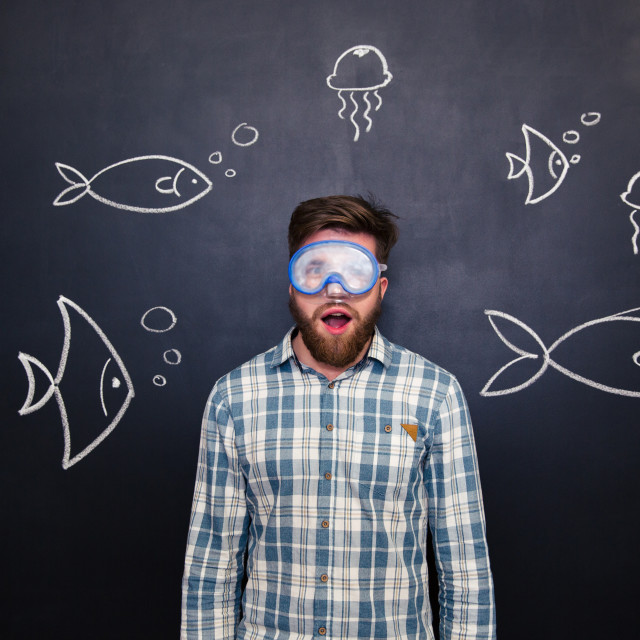 """""""Amazed man in diving mask with open mouth over blackboard"""" stock image"""