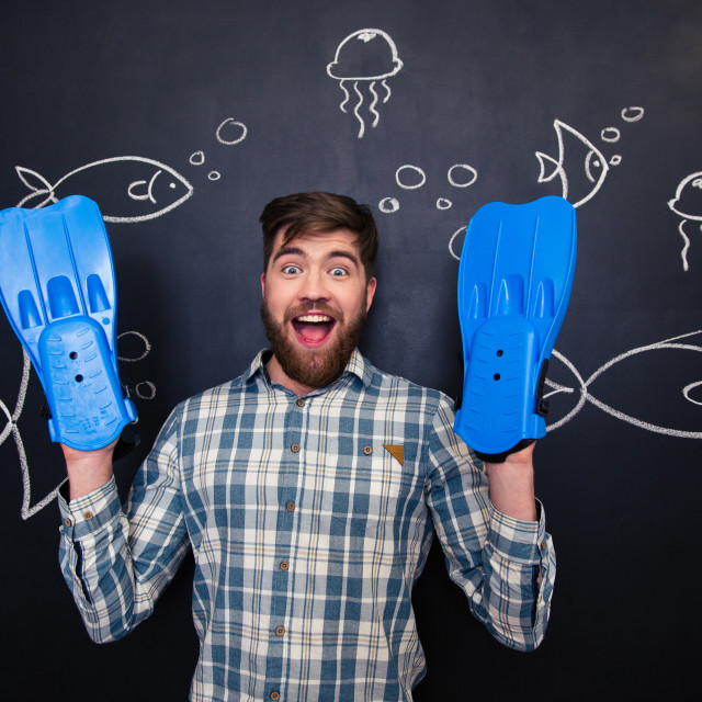 """""""Excited man with flippers on hands standing over blackboard background"""" stock image"""
