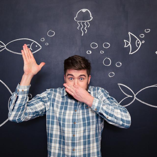 """Amusing man imitating diving in ocean over blackboard with drawings"" stock image"