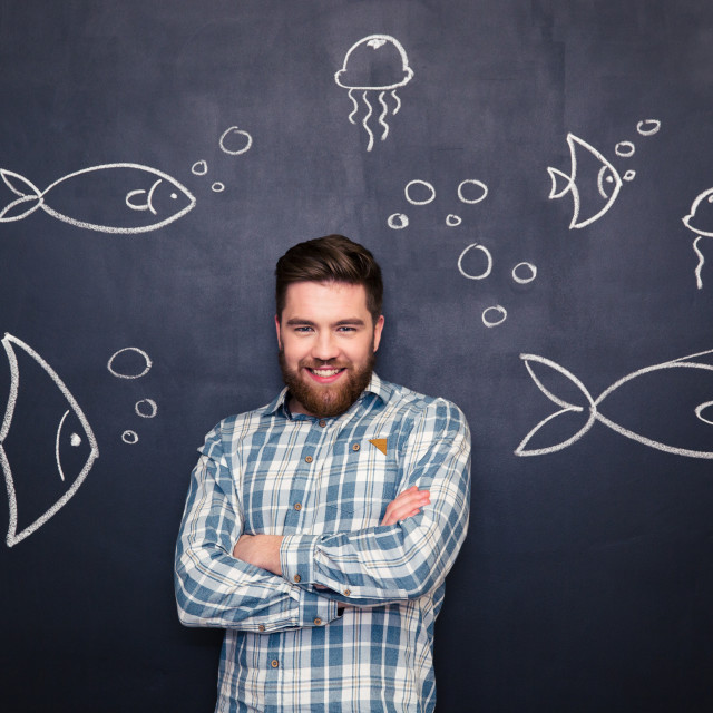 """""""Cheerful man standing over blackboard with drawn fishes and jellyfishes"""" stock image"""