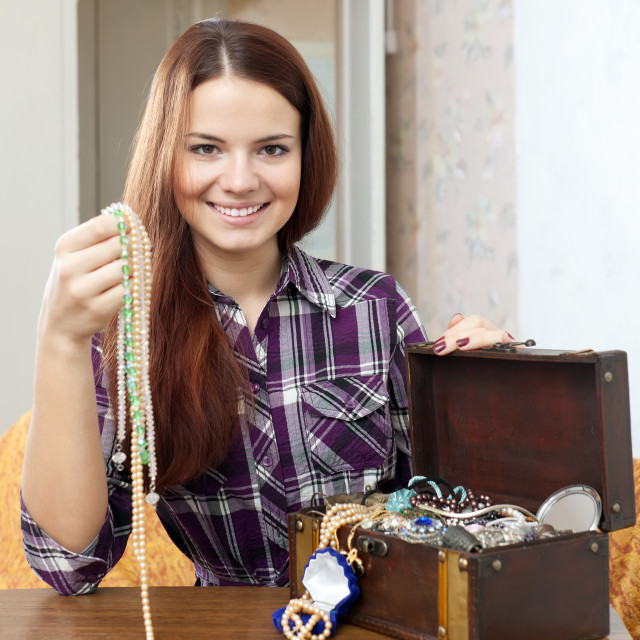 """woman chooses jewelry in chest"" stock image"