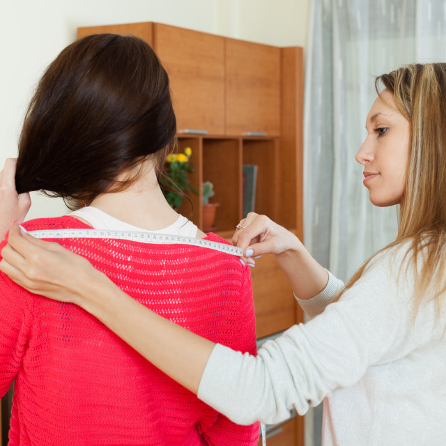 """Girl measuring the shoulders of friend shoulders"" stock image"