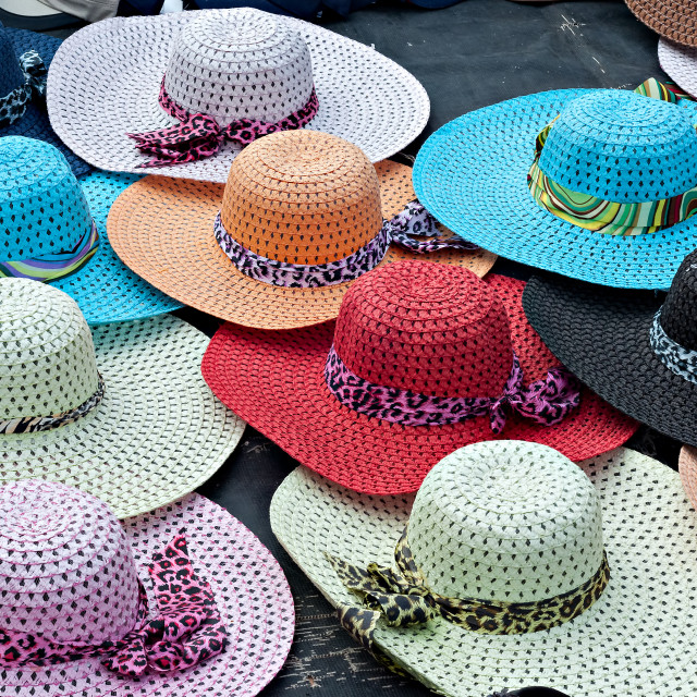 """Brightly colored wide brimmed ladies straw sun hats for sale at the beachfront"" stock image"