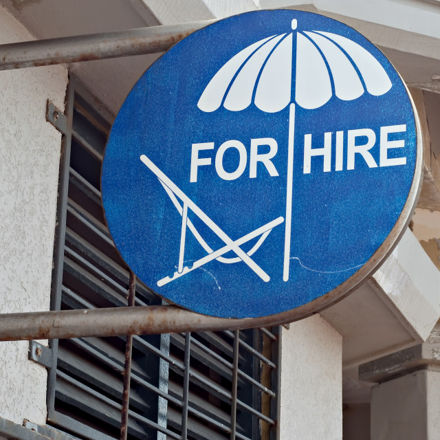 """Sign advertising beach chairs and umbrellas for hire"" stock image"