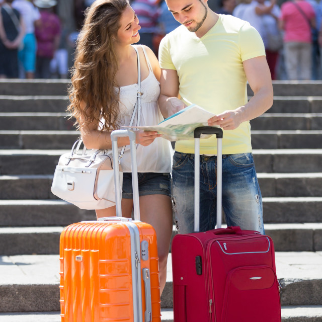 """Couple with luggage reading map"" stock image"