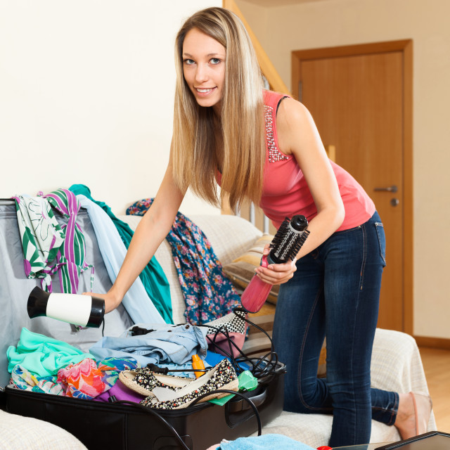 """girl trying to find room for all the things in trunk"" stock image"