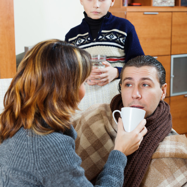 """unwell man surrounded by caring wife and son"" stock image"