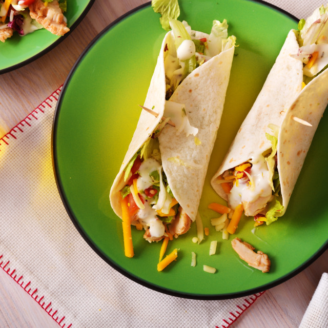 """Two khicken fajitas on green plate top view"" stock image"