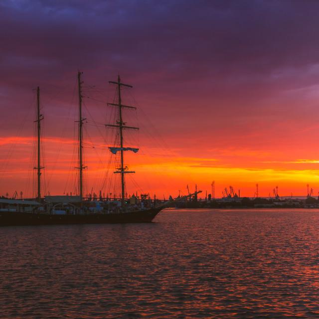 """Sail ship coming into port on sunset"" stock image"
