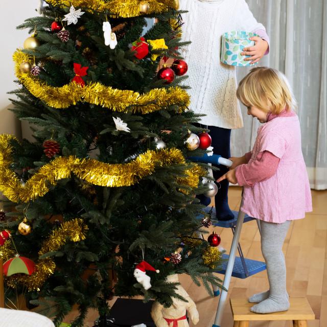 """Girls decorating christmas tree"" stock image"