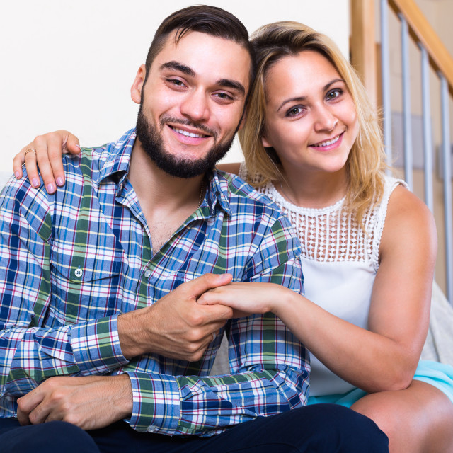 """""""Portrait of young couple sitting on couch."""" stock image"""