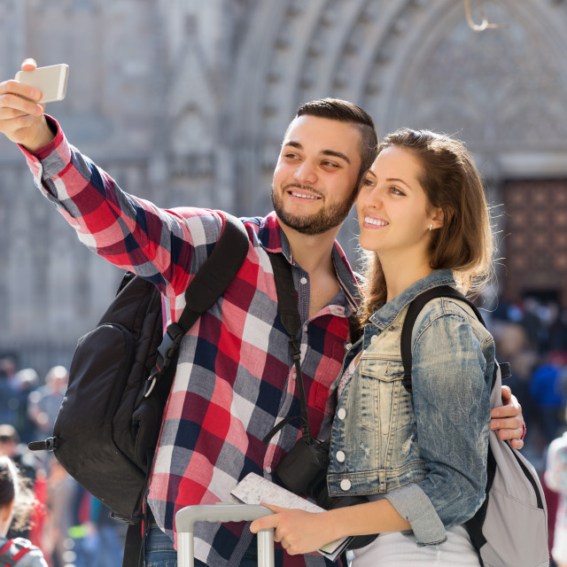 """""""Couple with luggage taking selfie"""" stock image"""
