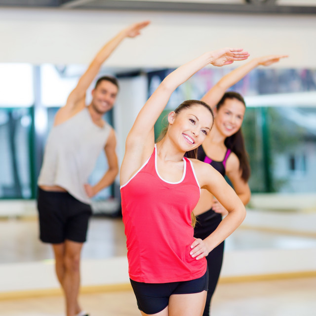 """group of smiling people stretching in the gym"" stock image"