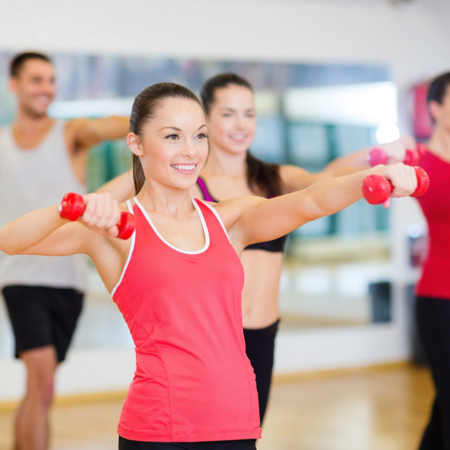 """group of smiling people working out with dumbbells"" stock image"