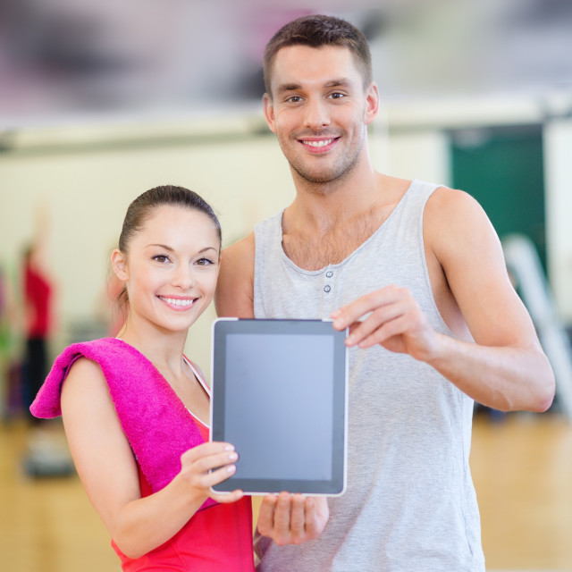 """two smiling people showing blank tablet pc screen"" stock image"
