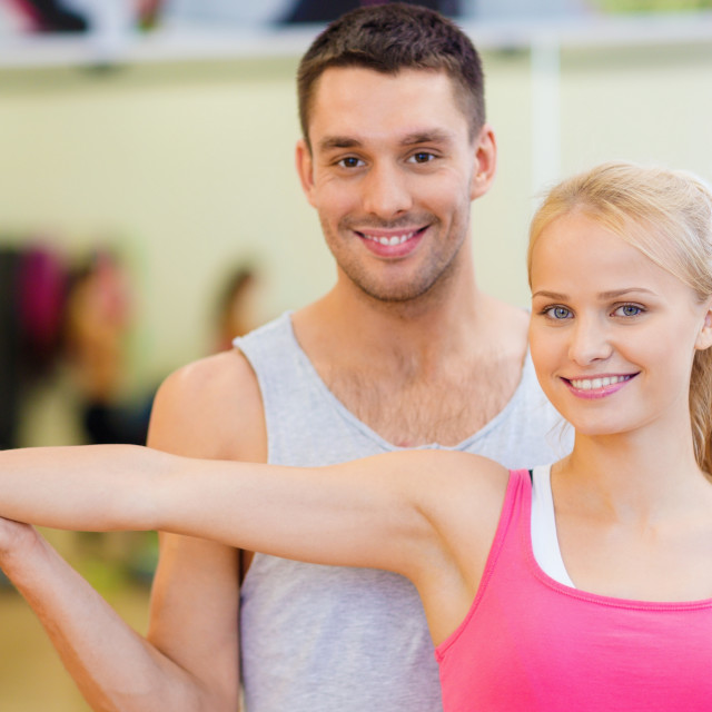 """male trainer with woman working out with dumbbell"" stock image"