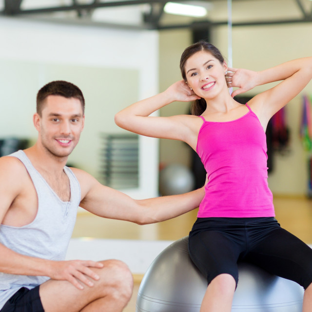 """male trainer with woman doing crunches on the ball"" stock image"