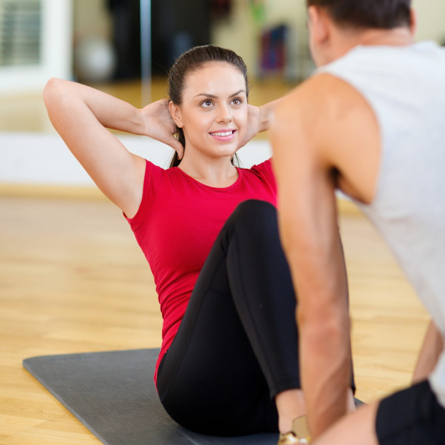 """male trainer with woman doing sit ups in the gym"" stock image"