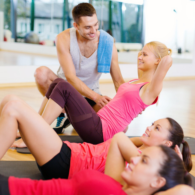 """group of smiling women doing sit ups in the gym"" stock image"