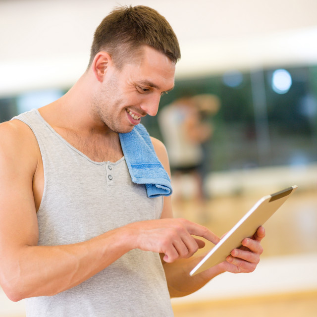 """young man with tablet pc computer and towel in gym"" stock image"