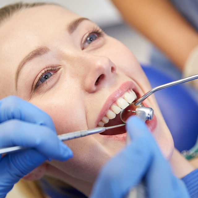 """close up of dentist treating female patient teeth"" stock image"