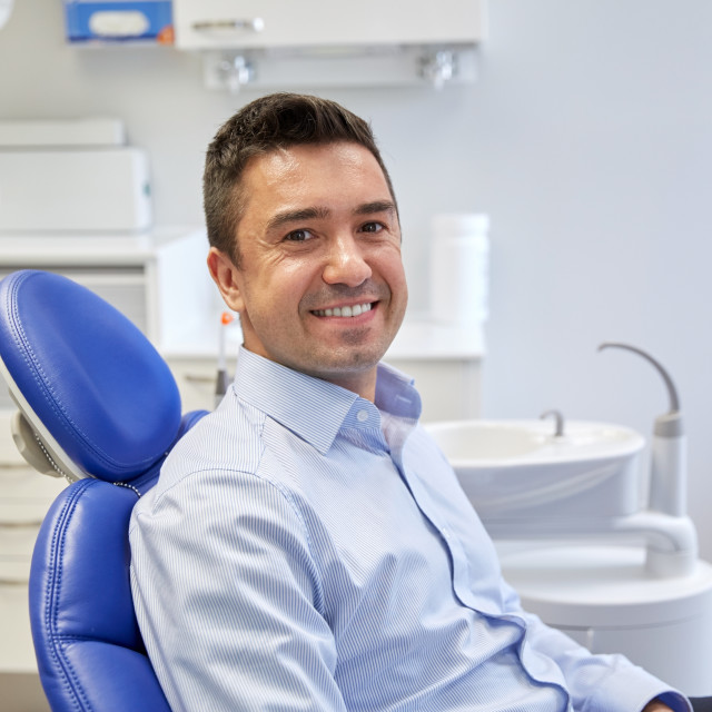 """happy male patient sitting on dental chair"" stock image"