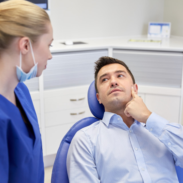 """male dentist with woman patient at clinic"" stock image"