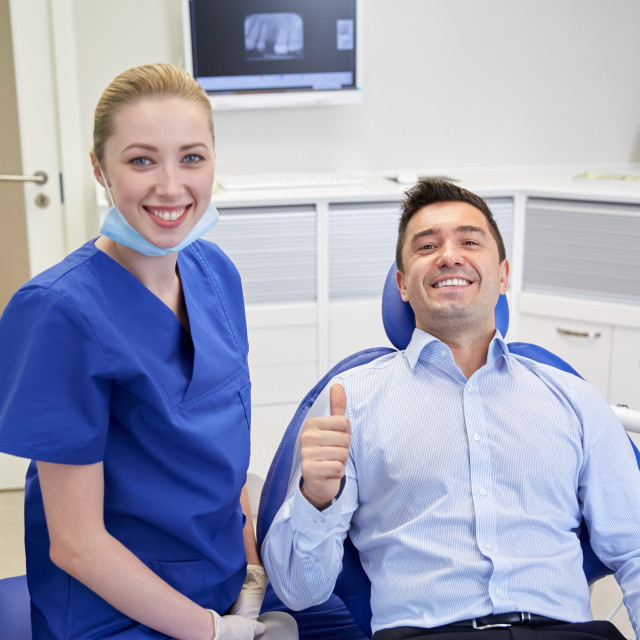 """happy female dentist with man patient at clinic"" stock image"