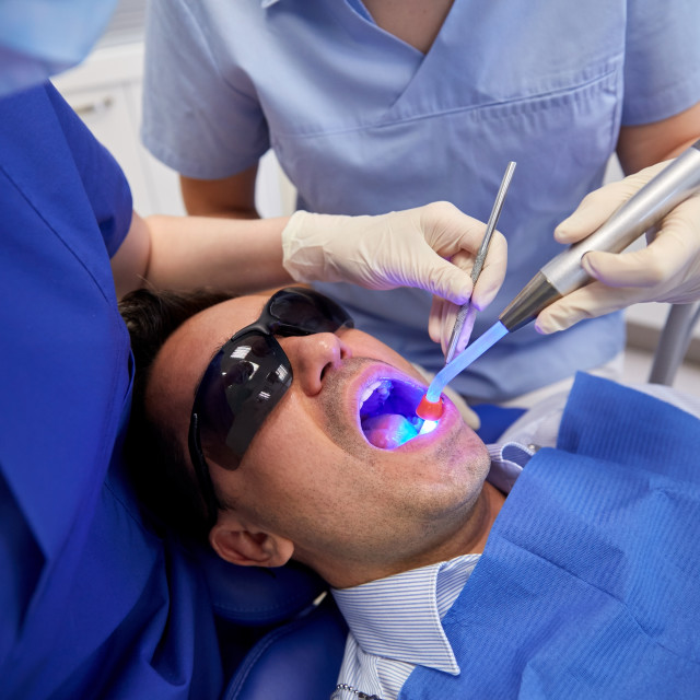 """dentists treating male patient teeth at clinic"" stock image"