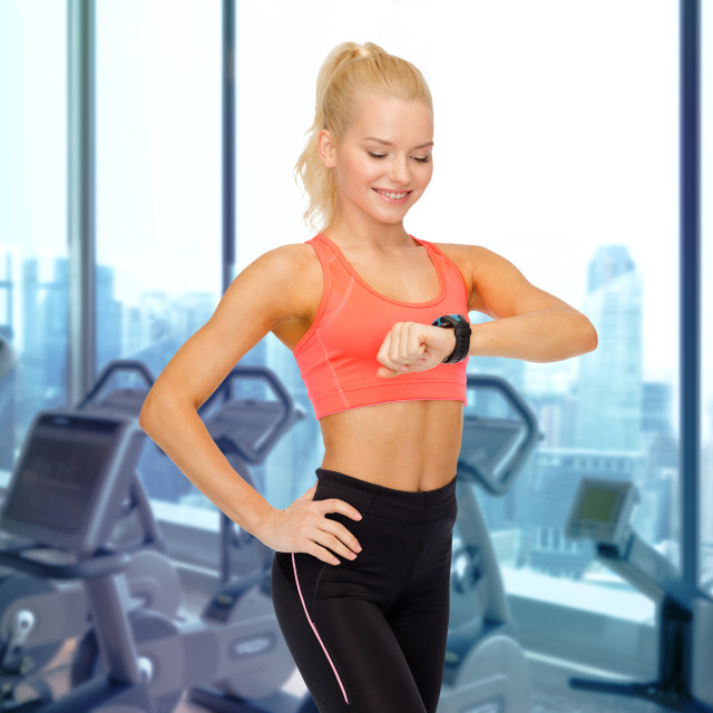 """smiling woman looking at heart rate watch in gym"" stock image"