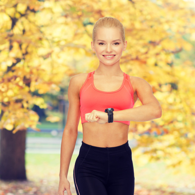 """""""smiling woman with heart rate monitor on hand"""" stock image"""