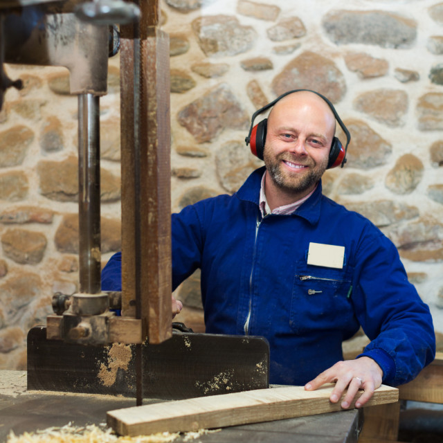 """Woodworker on lathe in workroom"" stock image"