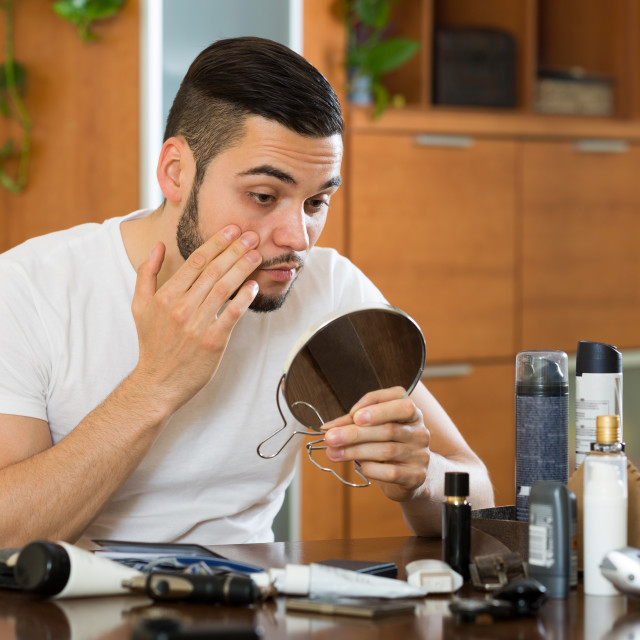 """""""Man checking eyelid in a mirror"""" stock image"""