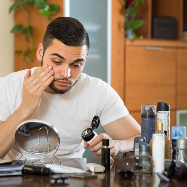"""Man applying cream on face skin"" stock image"