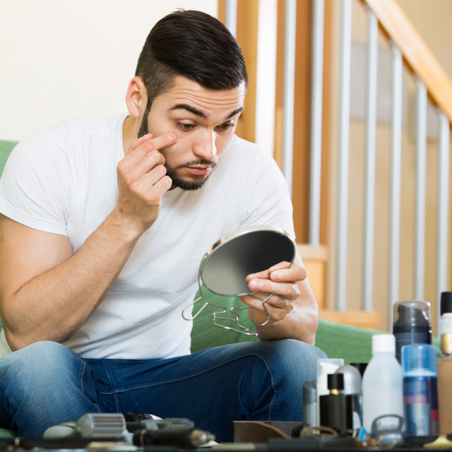 """""""Guy looking at his problematic skin in a mirror"""" stock image"""
