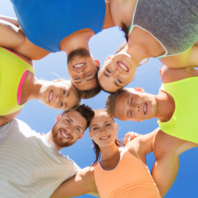 """group of happy sporty friends in circle outdoors"" stock image"
