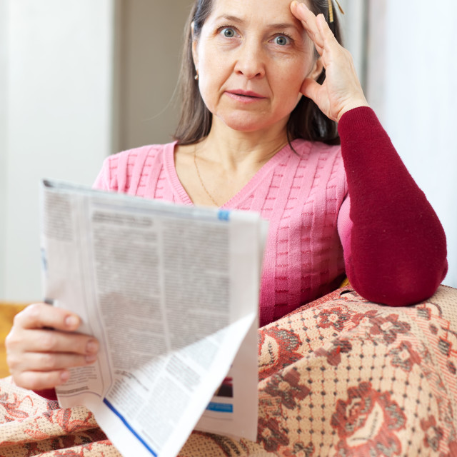 """""""affliction mature woman with newspaper"""" stock image"""