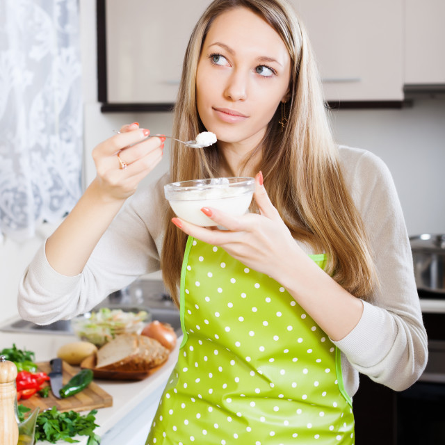 """Smiling woman in apron eating curd cheese"" stock image"